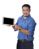 O homem asiático na mostra azul da camisa descreve com lablet Foto de Stock Royalty Free