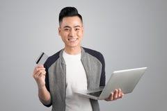O homem asiático novo com portátil e o cartão de crédito no estúdio isolaram g Foto de Stock