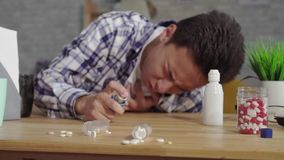 O homem asiático novo em uma camisa asmática com ataques do sufocamento usa um inalador mo lento video estoque