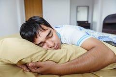 O homem asiático que dorme na cama, tempo de manhã imagem de stock