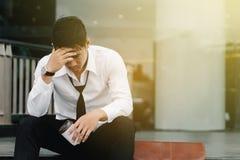 O homem asiático senta-se nas etapas de um prédio de escritórios com o esforço fotos de stock