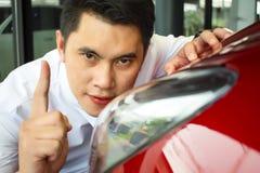 O homem asiático wipping o carro com farol do diodo emissor de luz fotografia de stock royalty free