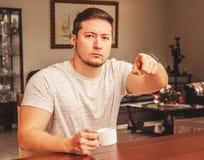 O homem assentou apontar o dedo para a frente com uma expressão séria imagem de stock