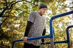 O homem ativo considerável saudável com o corpo muscular do ajuste que faz o exercício exercita Exterior, parque Esportes e conce imagens de stock royalty free