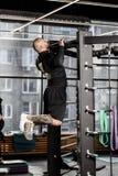 O homem atlético brutal vestido na roupa preta dos tipos levanta na barra no gym imagem de stock royalty free