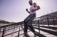 O homem atlético com a faixa em sua cabeça vestida no t-shirt branco, nas caneleiras pretas e no short azul está correndo abaixo  foto de stock royalty free