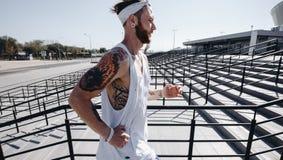 O homem atlético com a faixa em sua cabeça vestida no t-shirt branco, nas caneleiras pretas e no short azul está correndo acima foto de stock royalty free