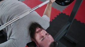 O homem atlético considerável executa a imprensa de banco no banco no gym video estoque