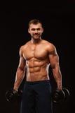 O homem atlético considerável no gym está bombeando acima muscles com pesos em um gym Corpo muscular da aptidão isolado na obscur fotos de stock royalty free