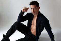 O homem atlético considerável novo que levanta no estúdio, vestindo na roupa preta, senta-se para baixo, no fundo branco fotos de stock royalty free