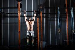 O homem atlético dá certo no gym com a barra imagem de stock royalty free