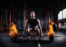 O homem atlético dá certo no gym com um barbell impetuoso foto de stock