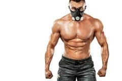 O homem atlético do halterofilista muscular forte brutal que bombeia acima muscles na máscara do treinamento no fundo branco work imagens de stock