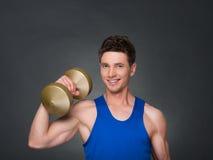 O homem atlético do poder considerável no treinamento que bombeia acima muscles com pesos em um gym Imagens de Stock Royalty Free