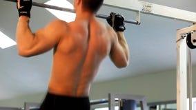 O homem atlético novo executa exercícios do músculo vídeos de arquivo