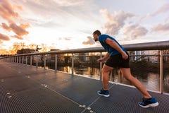 O homem atlético novo prepara-se para uma sprint corrida imagem de stock royalty free