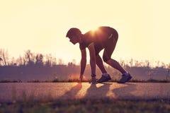 O homem atlético que começa nivelando movimentar-se no sol irradia imagens de stock royalty free