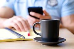 O homem atrás da xícara de café lê um texto fotografia de stock royalty free