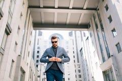 O homem atrativo com barba é andar exterior no fundo do prédio de escritórios Veste o t-shirt, calças de brim, óculos de sol Ele  foto de stock