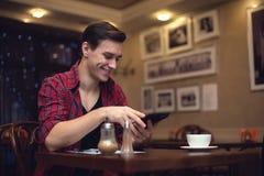O homem atrativo de sorriso dos jovens usa sua tabuleta dentro Imagem de Stock