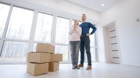 O homem atrativo está abraçando sua esposa bonita quando o explicar as questões básicas na decoração da casa nova vídeos de arquivo