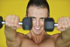 O homem atrativo forte executa exercícios usando uma faixa da resistência foto de stock royalty free