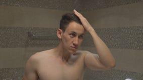 O homem atrativo novo endireita o penteado após um chuveiro no banheiro da sala de hotel vídeos de arquivo