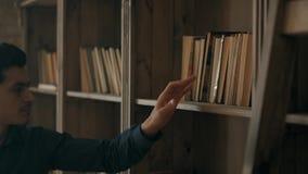 O homem atrativo novo está procurando o livro necessário na prateleira na biblioteca O estudante esperto está procurando filme