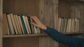 O homem atrativo novo está procurando o livro necessário na prateleira na biblioteca O estudante esperto está procurando video estoque