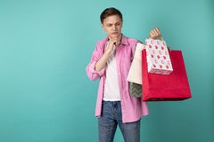 O homem atrativo novo na camisa cor-de-rosa est? estando pensativamente com sacos de compras ? disposi??o fotografia de stock