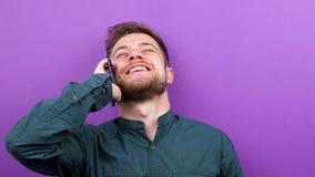 O homem atrativo novo puxa o telefone de suas calças e começa-o falar nele e ri-o video estoque