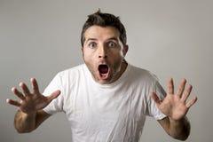 O homem atrativo novo surpreendido surpreendeu na expressão da cara da surpresa de choque e na emoção de choque Foto de Stock Royalty Free