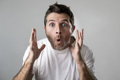 O homem atrativo novo surpreendido surpreendeu na expressão da cara da surpresa de choque e na emoção de choque fotos de stock