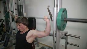 O homem aumenta a barra no gym vídeos de arquivo