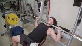 O homem aumenta a barra no gym video estoque
