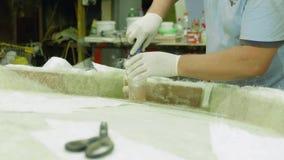 O homem aumenta a construção de madeira com revestimento do gel e fibra sintética vídeos de arquivo