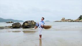 O homem aumenta a menina em seus braços e circunda-a ao redor Os pares novos na roupa azul voam para fora no Sandy Beach vídeos de arquivo