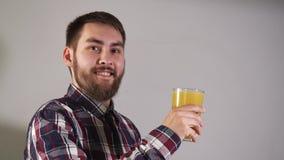 O homem aumenta o vidro do close up e do olhar do suco de laranja na câmera com sorriso 4K filme