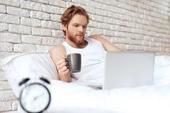 O homem awakining de cabelo vermelho encontra-se na cama com portátil imagem de stock