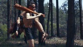 O homem bárbaro muscular com um bastão está levando uma mulher em seu ombro video estoque