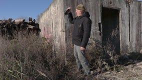 O homem bêbado com a garrafa de vinho vazia próximo abandonou a construção vídeos de arquivo