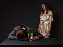 O homem bêbado está dormindo na tabela com a garrafa na mão, Fotos de Stock Royalty Free