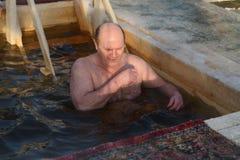 O homem banha-se na água fria do gelo-furo no dia do esmagamento Rússia Fotografia de Stock Royalty Free