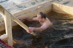 O homem banha-se na água fria do gelo-furo no dia do esmagamento Rússia Fotos de Stock Royalty Free