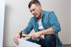 O homem bateu seu polegar com mobília de montagem do martelo fotos de stock