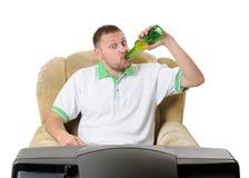 O homem bebe a cerveja e presta atenção à tevê Fotos de Stock