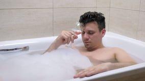 O homem bebido é cair adormecida com vidro de vinho no banho e deixa cair o vidro na água filme