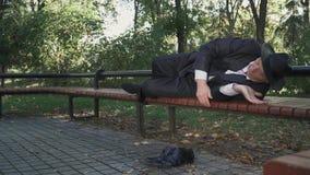 O homem bebido coloca confortável no banco no parque vídeos de arquivo