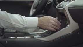 O homem bem sucedido não reconhecido que senta-se no veículo e inspeciona comprou recentemente auto do concessionário automóvel C video estoque