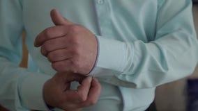 O homem bem sucedido no terno azul endireita suas luvas, close-up filme